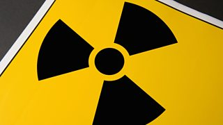 The radiation warning sign. A black circle with three triangular blades on a yellow background.