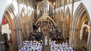 Clergy, choir and congregation under the large concrete arch in the nave of Llandaff Cathedral during a service
