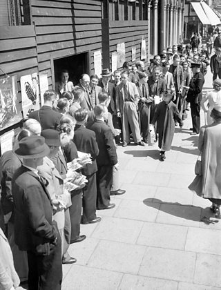 Men in WWII era clothing form a large queue.