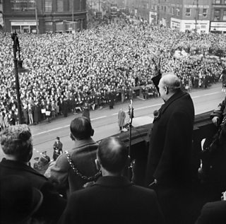 Winston Churchill standing on a balcony in front of a massive crowd giving the 'V for victory' hand gesture.
