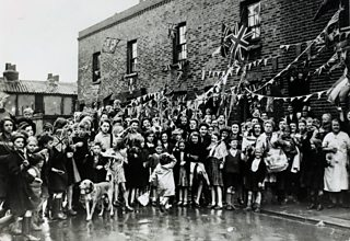 Large group of people smiling and waving in front of their terraced houses adorned with bunting and flags.