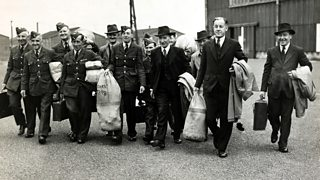 A group of smiling men carrying duffel bags. Some are in uniform, others are in civilian clothing.