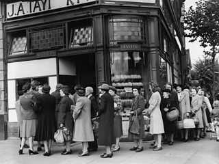 Women in 1940s clothing queue with baskets outside a bakery.