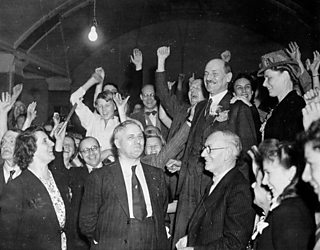 Clement Attlee celebrates surrounded by a cheering crowd.
