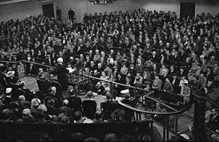 William Beveridge addresses a crowd from a podium in a hall.