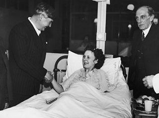 Aneurin Bevan smiles and shakes the hand of a female patient in a hospital bed.