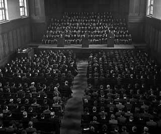 A large school hall filled with uniformed pupils sitting in rows of chairs.
