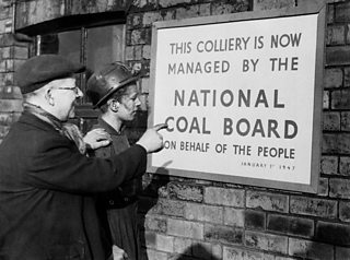 Two men, one in a mining helmet look at a poster that reads; This colliery is now managed by the National Coal Board on behalf of the people.