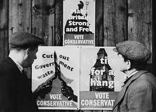 Two men in flat caps look at a series of posters for the Conservative Party on a wall. Text: Cut out Government waste. Vote Conservative.