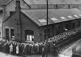 A very large number of men in flat caps queue around a building