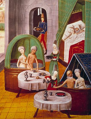Medieval illustration showing a public bathhouse, the bathers are being waited on by servants