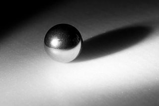 Abstract shot of a metal ball bearing on a white background