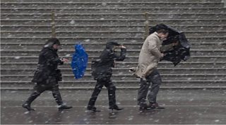 Three people walking through snow and strong winds.