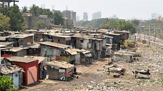 Stryd slym yn Mumbai, India. Mae trac rheilffordd yn mynd heibio casgliad o dai simsan, a gallwch weld adeiladau uchel yn y cefndir.