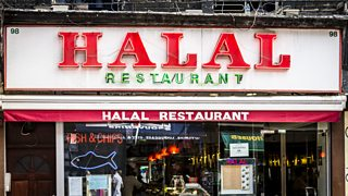 A typical high street store. The sign over the store reads Halal Restaurant.