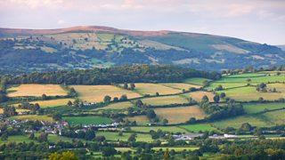 Tirwedd â phoblogaeth wasgaredig ger Crughywel, Powys. Mae ychydig o adeiladau preswyl i'w gweld yn y blaen, a bryniau gwyrdd a choedwigoedd i'w gweld yn y cefn.