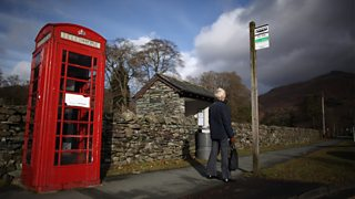 An elderly person waits at a rural bus stop. Next to the bus stop is a traditional red telephone box.