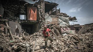 A boy stands on a pile of rubble amongst houses destroyed by an earthquake in Kathmandu, Nepal.