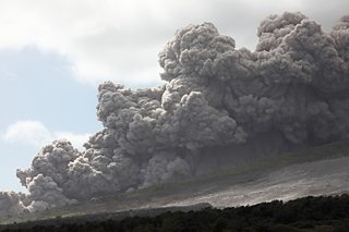 A large cloud of volcanic material flowing down the side of a mountain.