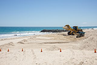 Two bulldozers re-profiling a beach in Western Australia.