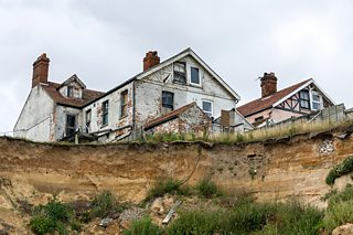 Eroded cliffs at Happisburgh, Norfolk. The coastline has reached buildings which are now abandoned.