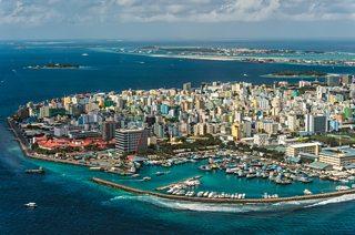 Golygfa o'r awyr o Malé, prifddinas y Maldives. Mae wal fôr goncrit fawr o amgylch y ddinas i'w hamddiffyn rhag y môr.