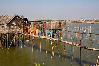 Traditional stilt houses standing in water, with high rise apartment buildings in the background.