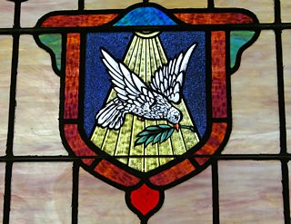 Stained glass window depicting a dove holding a branch in its beak
