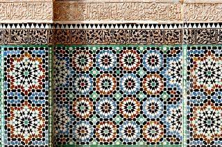 Caligraffeg Islamaidd a phatrymau geometrig lliwgar o waliau mosg Ben Youssef ym Marrakesh, Moroco.