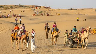 Tourists in a desert landscape. Some are walking in the distance. In the foreground some are riding camels that are being led by guides.