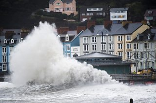 A large wave breaks on the seafront wall pushing white spray high into the air.