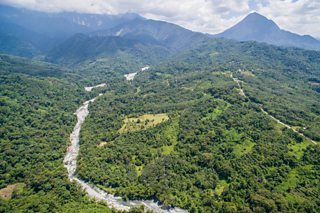 Aerial view of a river flowing through a hilly tropical landscape with mountains in the background.