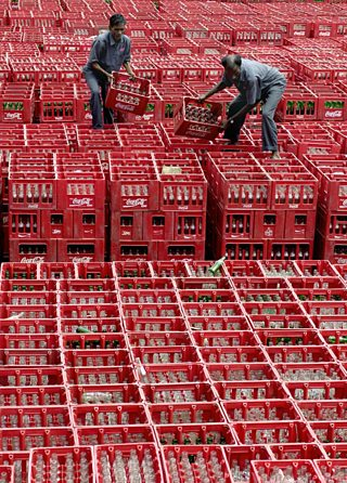 Indian employees at Hindustan Coca-Cola stack a pile of empty bottles in their crates.