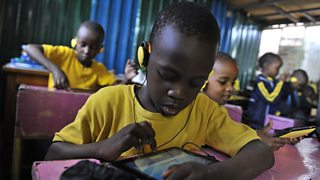 Children sitting in classroom using tablets. Some are wearing headphones.