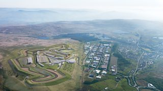 An aerial view of a race track next to apopulated area with mountains in the distance.