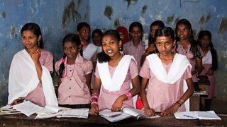 Indian girls in school uniform standing at their desks