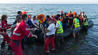Aid workers in uniform help refugees out of an inflatable boat on a beach