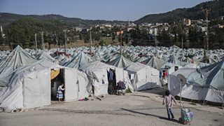 A sea of tightly packed tents and shelters with children playing in the foreground