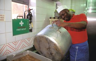 Catering worker washing up a large saucepan