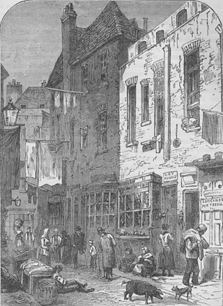 An illustration of St Giles rookery, London in 1850. Some people are walking in the street whilst others are lying on the floor next to a pig and a cat. Blankets are hanging from poles in the street