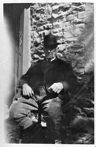 Grainy black and white photograph of an elderly man in a bowler hat and suit