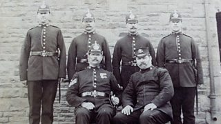 Grainy black and white photograph of six policemen posing for the camera wearing police uniform