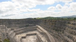High angle view of limestone quarry with layers of quarried rock descending in a step-like structure