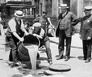 Prohibition 1920s. Agents pouring liquor into sewer following a raid during probibition, New York City, NY, USA. Photo c.1921