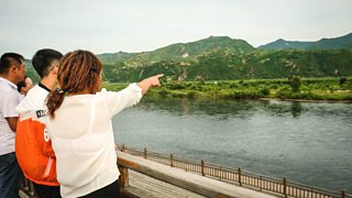 Chinese tourists look across the Yalu river border into North Korea