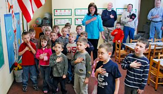 Children say the Pledge of Allegiance to the American flag in nursery school