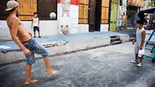 Boys playing football on the street
