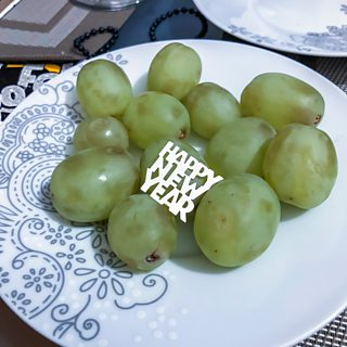 Grapes on a plate with sequin reading Happy New Year