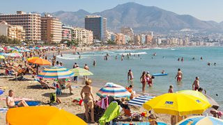 Buildings, sea and beach with people in Fuengirola