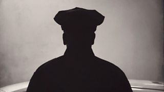 A silhouette of an American policeman from torso upwards, facial features obscured.
